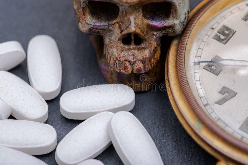 Pojęcie dla którego dzwonkowe opłaty drogowe: antykwarski kieszeniowy zegarek, rzeźbiąca czaszka i medyczne pigułki na naturalnym fotografia stock