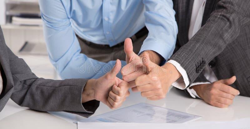 Pojęcie dla pomyślnej pracy zespołowej: ludzie biznesu robi kciukom u zdjęcie royalty free