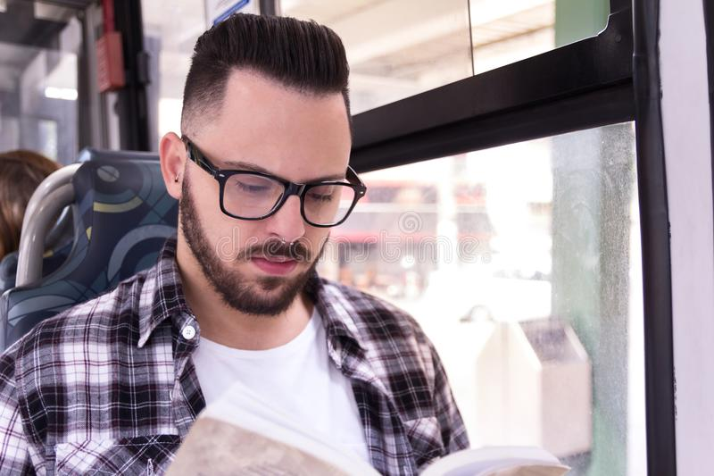 Pojęcie dojeżdżać do pracy, ruchliwość Studenta uniwersytetu mężczyzna obsiadanie i fotografia stock