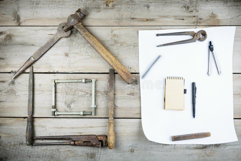 Pojęcie dom w budowie Stary drewniany desktop Starzy ośniedziali ciesielek narzędzia fotografia royalty free