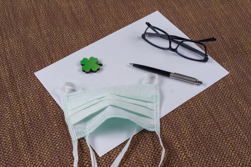 Pojęcie ekologia, natury ochrona Tło - czyści papier, liść zielona koniczyna i ochronną maskę, zdjęcie stock