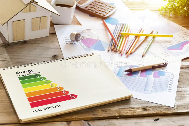 Pojęcie ekologiczny i życiorys energiczny dom Energii klasa Biurko swój miejsce, domów modele, kredki, żarówki, filiżanka, kalkul zdjęcia royalty free