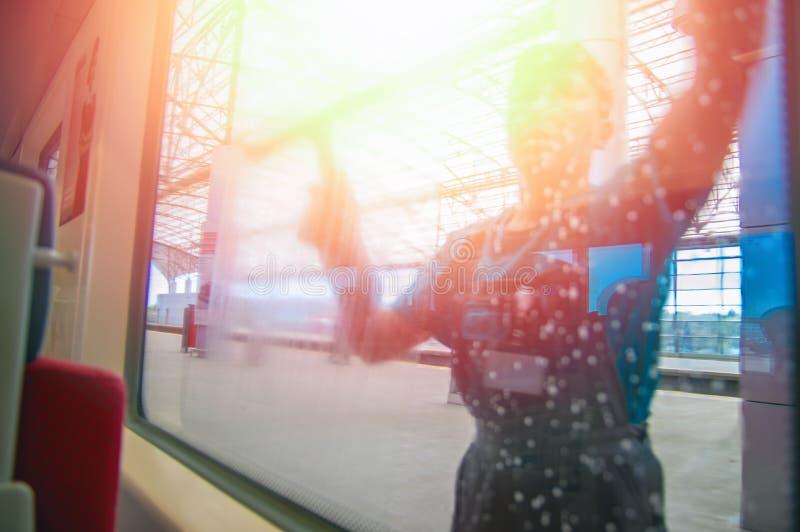 Pojęcie higiena na transporcie publicznym Sylwetka mężczyzna płuczkowy okno w pociągu przy nowożytną stacją kolejową obraz royalty free