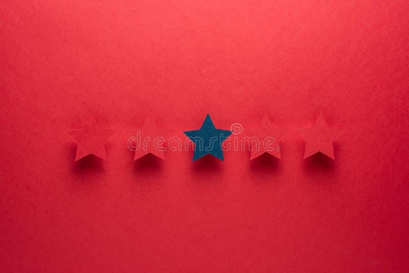 Pojęcie informacje zwrotne lub doborowość jest różny od everyone, był pierwszy błękitna gwiazda stoi za czerwieni przeciw obrazy royalty free