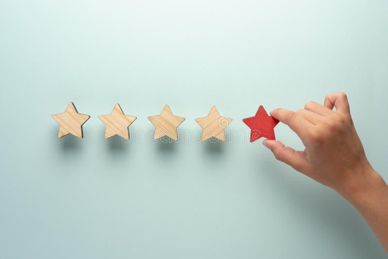 Pojęcie informacje zwrotne pięć gwiazd Ręka dodaje czerwoną gwiazdę cztery ordynariusz ones obrazy stock