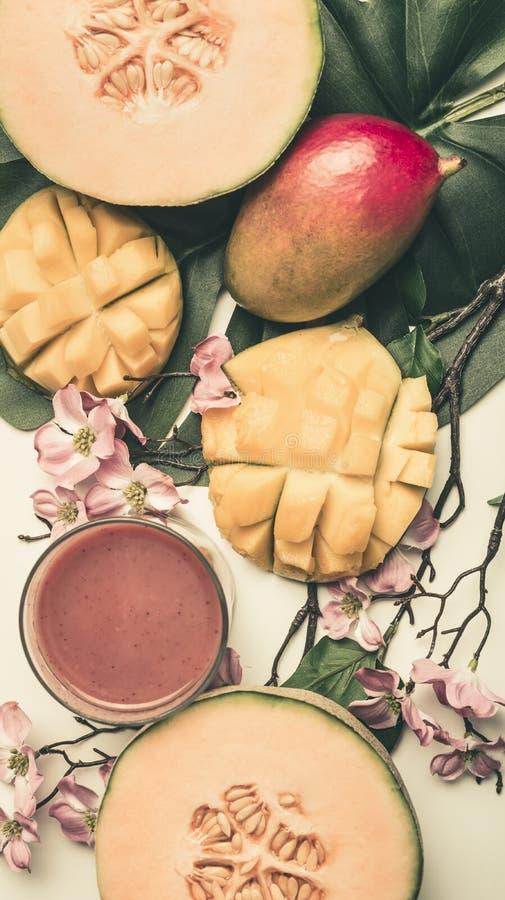 Pojęcie jedzenie, świeży pokrojony mango i melon z smoothies jarski, zdrowy, z kwiatami i liśćmi monstera, odgórny widok obraz stock