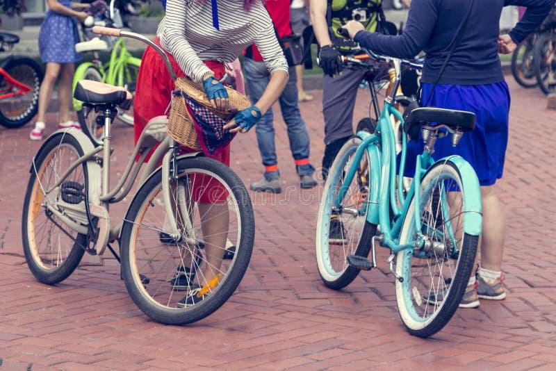 Pojęcie: kobiety na bicyklach Kobieta w jaskrawych ubraniach trzyma handlebars zdjęcia stock