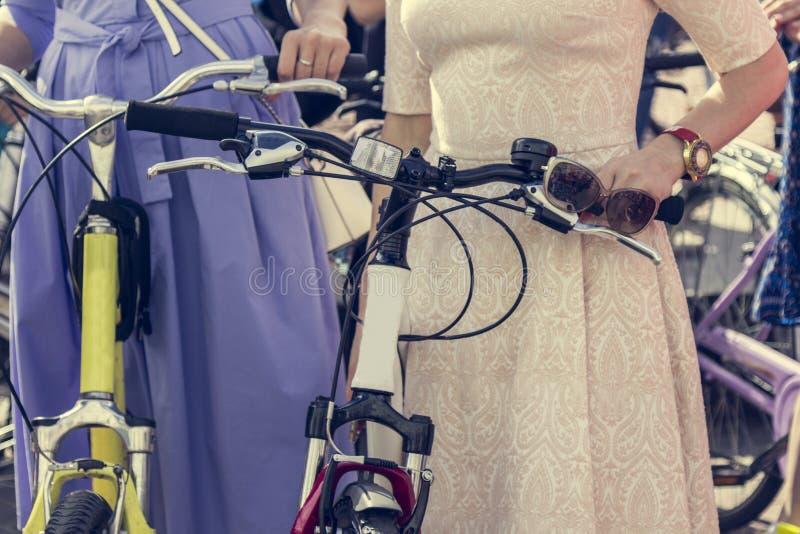 Pojęcie: kobiety na bicyklach Kobieta w jaskrawych ubraniach trzyma handlebars Część obrazek zdjęcia stock
