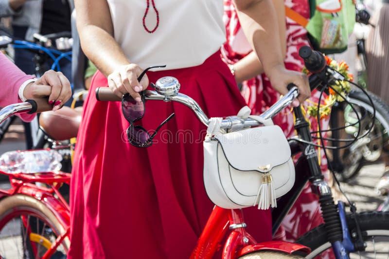 Pojęcie: kobiety na bicyklach Ręki trzyma handlebars W jego prawa ręka okularach przeciwsłonecznych Biała torba na kierownicie obraz royalty free