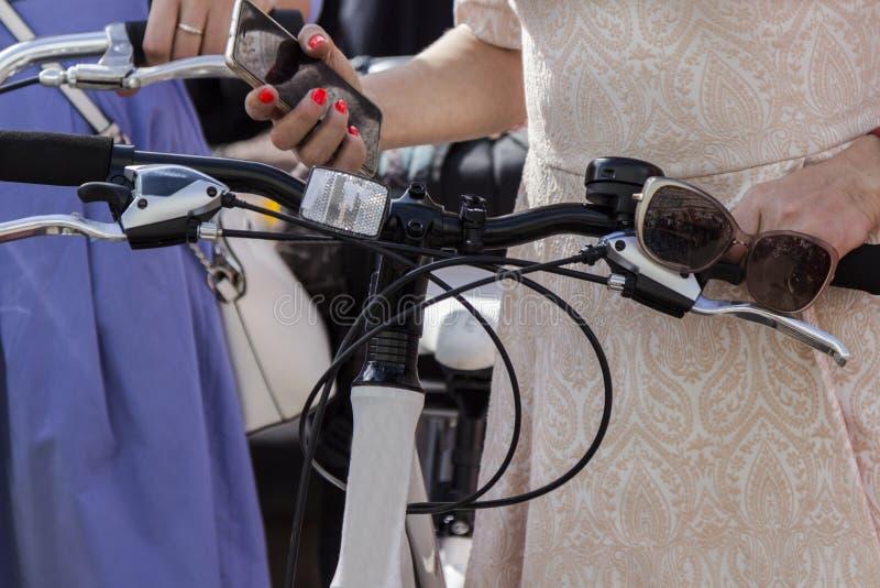 Pojęcie: kobiety na bicyklach Ręki trzyma handlebars w prawa ręka telefonie w lewych okularach przeciwsłonecznych, Część obrazek zdjęcia royalty free