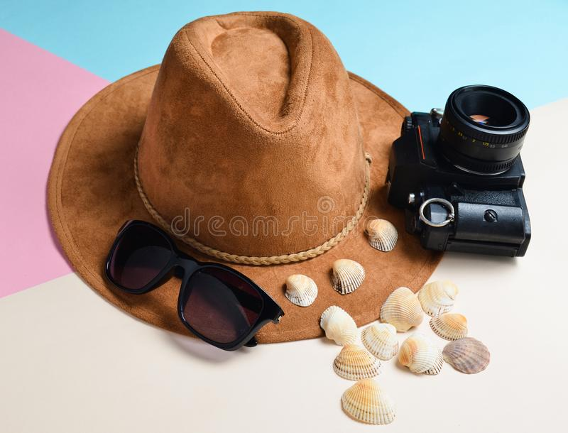 Pojęcie kurort na plaży Odczuwany kapelusz, okulary przeciwsłoneczni, rocznik ekranowa kamera, seashells na barwionym papierowym  zdjęcia stock