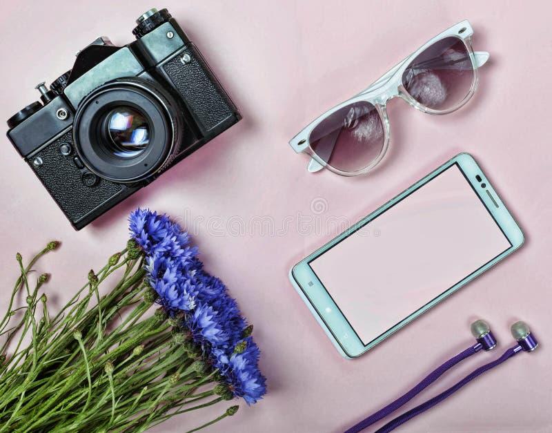 Pojęcie minimalizm, wakacje Antyczna kamera, modnisiów szkła, hełmofony, biały smartphone, piękny bukiet cornfl fotografia stock