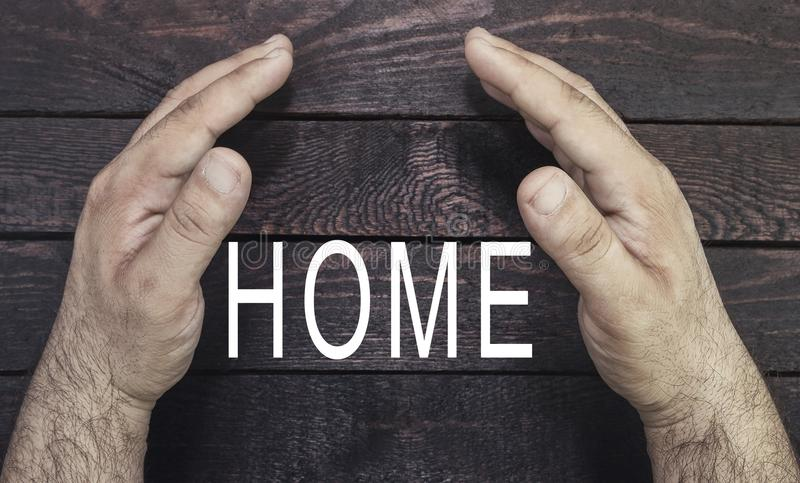 Pojęcie ochrona własność, domowy ubezpieczenie Asekuracyjnego agenta ` s ręk protectubg domu tekst na drewnie zdjęcie stock