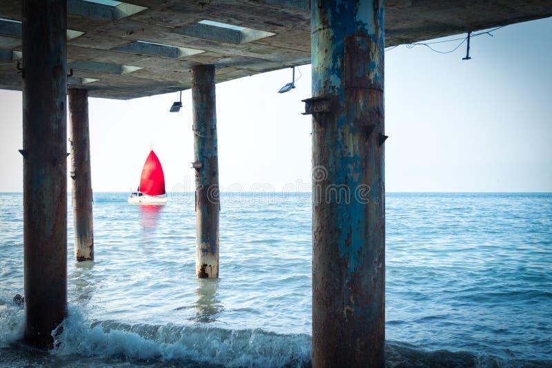 Pojęcie odkrycie, nadzieja i podróż, - żaglówka z czerwonym żaglem unosi się morzem Widok od starych filarów molo zdjęcie stock