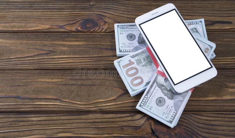Pojęcie pieniądze na drzewnym tle i telefon Pomysł biznes, gadżet, smartphone zastosowanie obraz stock