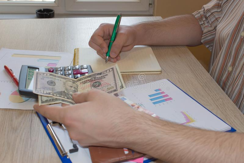 Pojęcie pieniężny planowanie, savings Mężczyzna, pieniądze z kalkulatorem i notatnik na drewno stole, Fotografia pokazuje zbliżen obraz royalty free