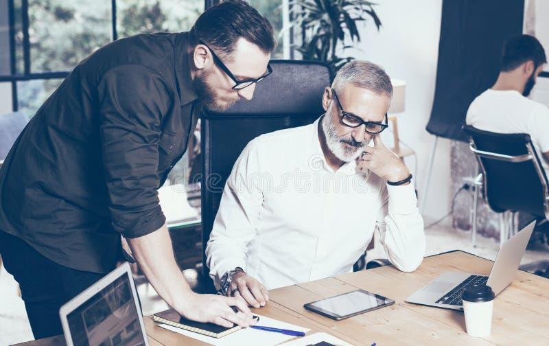 Pojęcie prezentacja nowy biznesowy projekt Młody brodaty mężczyzna dyskutuje pomysły z obrachunkowym kierownikiem w nowożytnym bi fotografia stock