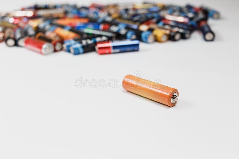 Pojęcie przetwarzać, Alkaliczna bateria kłama na stole na tle zamazane alkaliczne baterie w zdjęcie stock