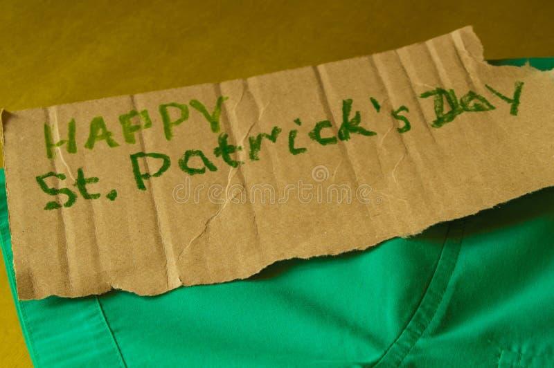 Pojęcie przygotowanie dla świętowania St Patrick ` s dzień, zielona koszula kłama na stole, tekst, Złoty tło zdjęcia royalty free