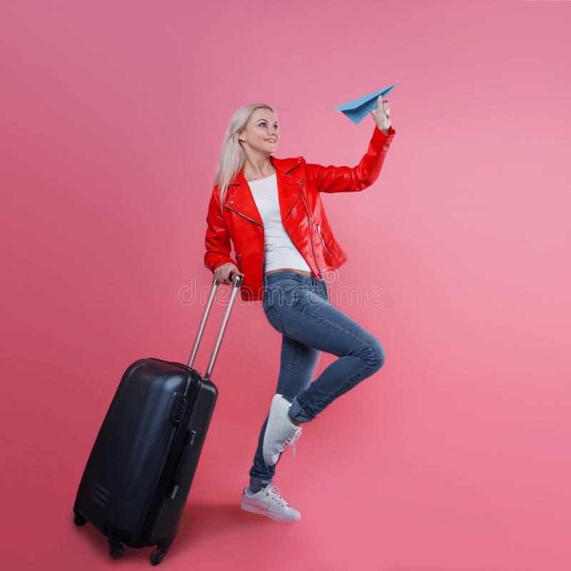 Pojęcie, przygotowywający ono potykać się Młoda kobieta z podróży walizką wszczyna papierowego samolot Blondynki turystyczna dzie obrazy royalty free