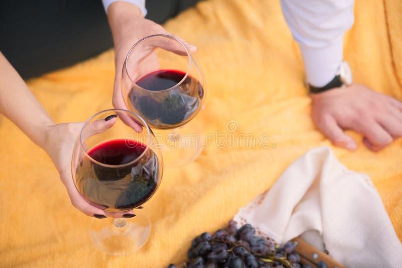 Pojęcie relaksować kochającej pary na pinkinie Kobiety i samiec ręki trzyma szkła z winem przeciw tłu yello zdjęcie royalty free