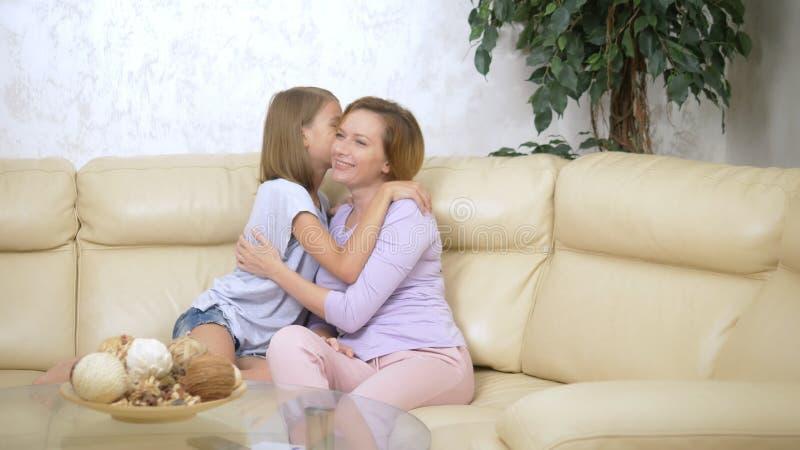 Pojęcie rodzinny zaufanie, szczęśliwa córka szepcze sekret jej macierzysty obsiadanie na kanapie w żywym pokoju obrazy stock