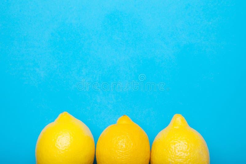 Pojęcie, trzy świeżej cytryny na błękitnym tle, opróżnia przestrzeń dla teksta fotografia stock