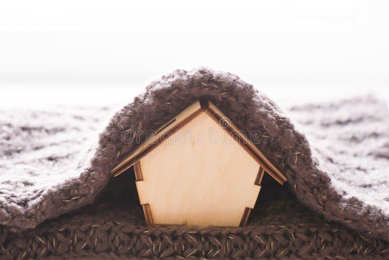 Pojęcie układ drewniany dom z szalikiem, oferta ciepłym budynek mieszkalny na białym tle/ Grzejny sezon obraz royalty free