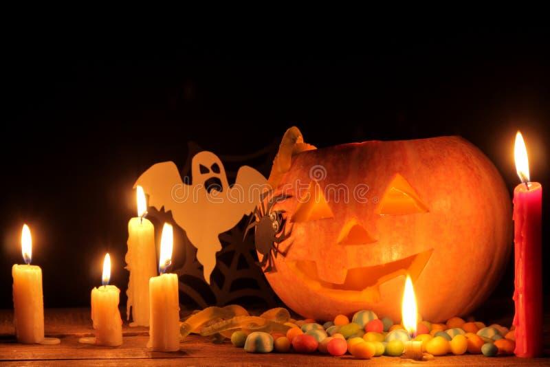 Pojęcie wakacje Halloween Halloweenowa bani głowa z świeczkami inside na drewnianym stole na czarnym backgr i wokoło fotografia stock