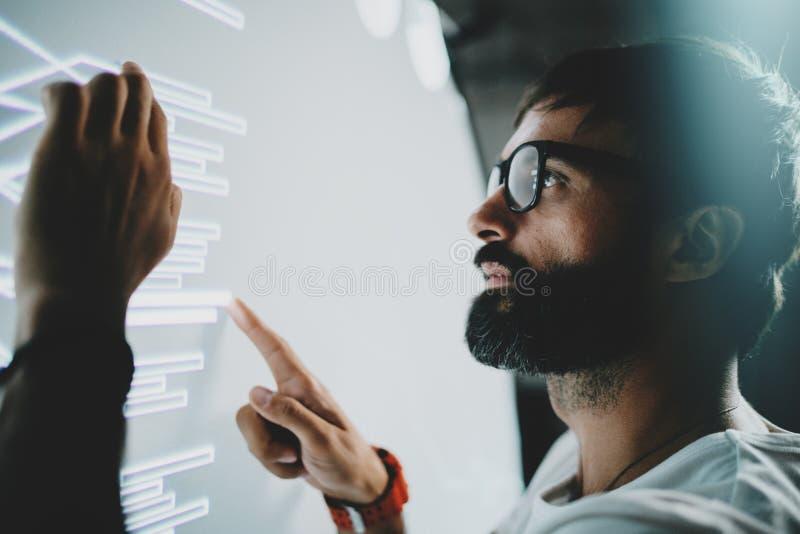 Pojęcie wirtualny ekran wyświetlacza, diagram, cyfrowi wykresów interfejsy Młody brodaty mężczyzna dotyka wirtualnego panelu z wy zdjęcie stock