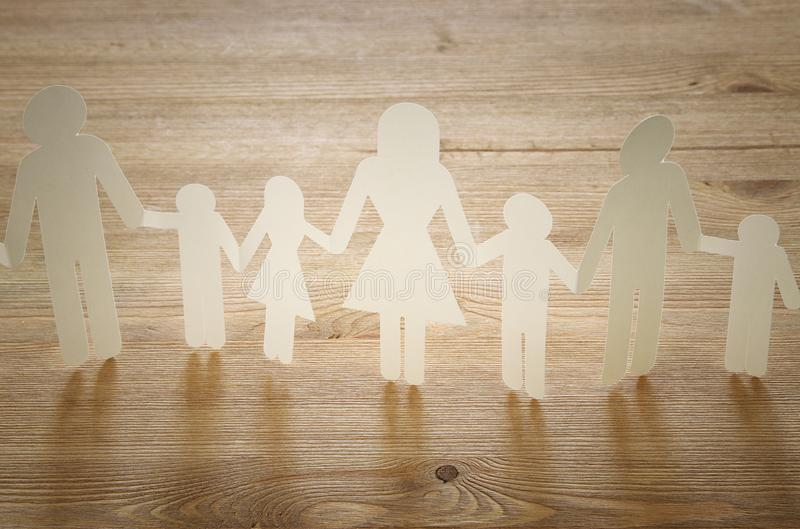 pojęcie wizerunek rodzina papieru łańcuchu wycinanki mienia ręki nad drewnianym stołem, zdjęcia royalty free