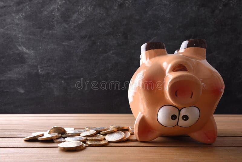 Pojęcie wydawać savings z prosiątko bankiem do góry nogami obrazy royalty free