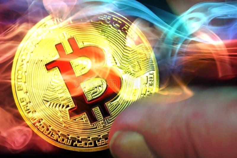 Pojęcie Złotych bitcoins wirtualne monety w ręce z kolorowym dymem obrazy stock