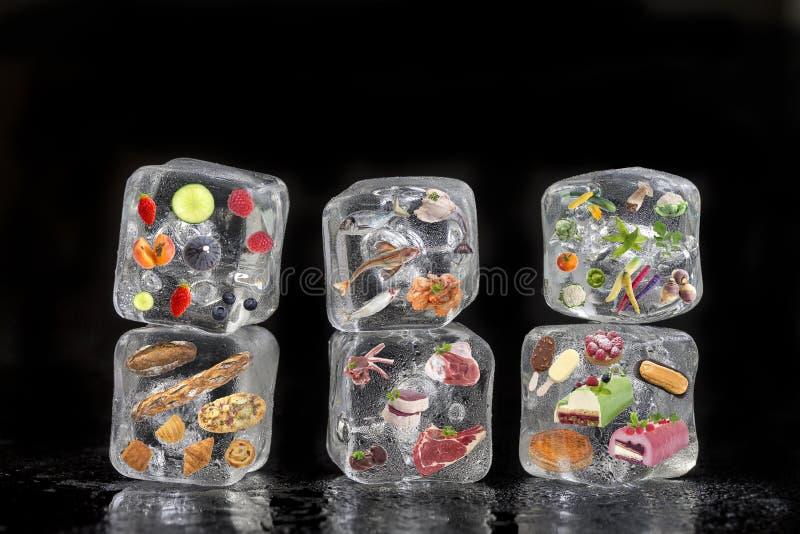 Pojęcie zamarznięci produkty: owoc, warzywa, fishs, mięso, pikantność ziele, ciasto, marznęli wśrodku kostek lodu na czerni zdjęcia stock