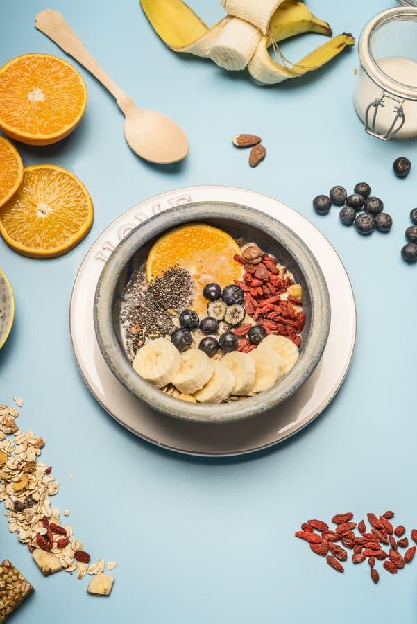 Pojęcie zdrowy śniadanie, jagody, banany, pomarańcze, zboża i mleko w rocznika pucharze na błękitnym tle, przestrzeń dla tex obraz royalty free