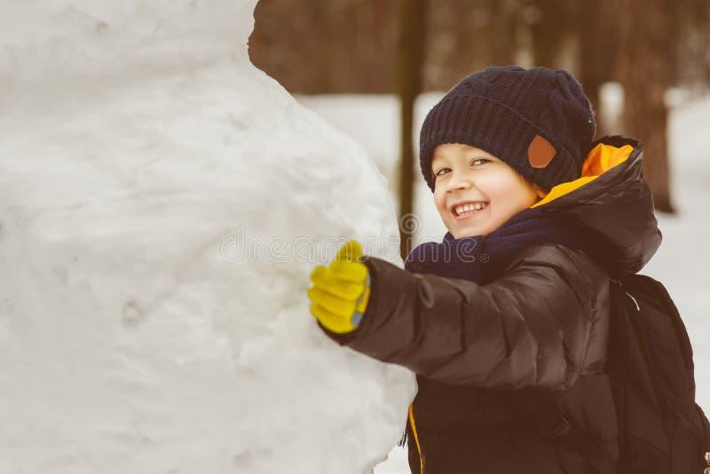 Pojęcie zim aktywność Szczęśliwa chłopiec pozycja obok bałwanu plenerowego zdjęcie royalty free