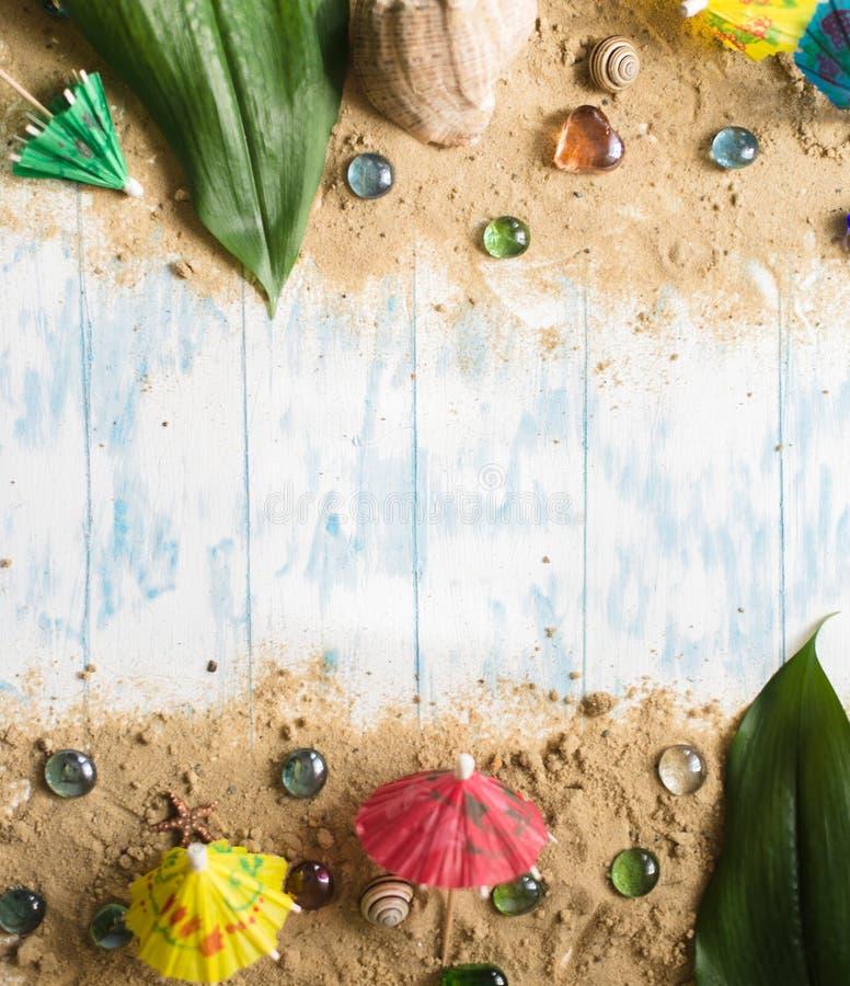 poj?cia t?a ramy piasek seashells lato Parasole dla koktajli/l?w na piasku na drewnianym tle z otoczakami fotografia stock