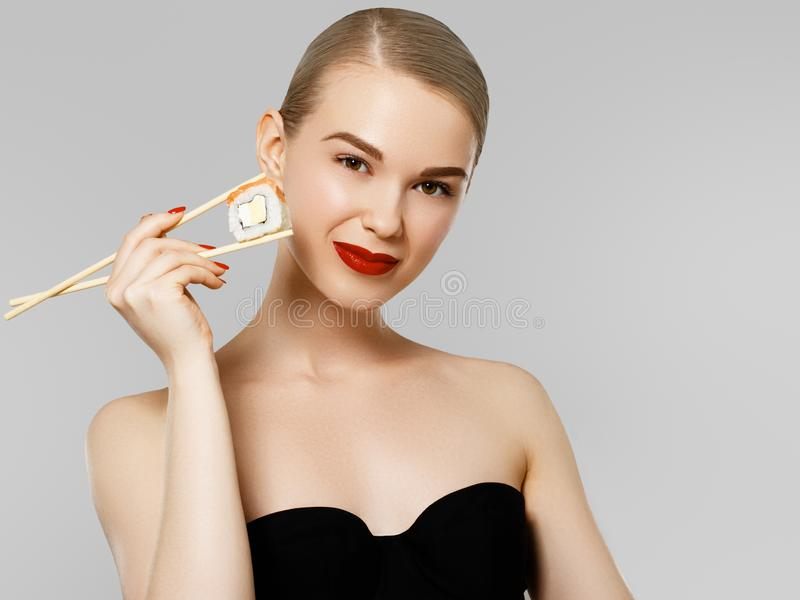 poj?cie diety od?ywczy Piękna Uśmiechnięta kobiety łasowania suszi rolka Z Chopsticks moda portret pi?kno model fotografia stock