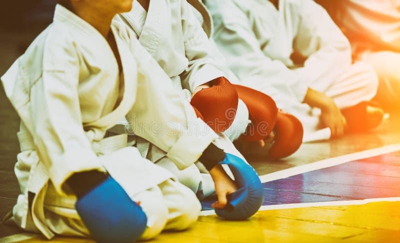 Poj?cie karate, sztuka samoobrony uczestnicy siedz? w oczekiwaniu na walki Przyw?dctwo, odpowiedzialno??, ch?? post?powa? zdjęcia royalty free
