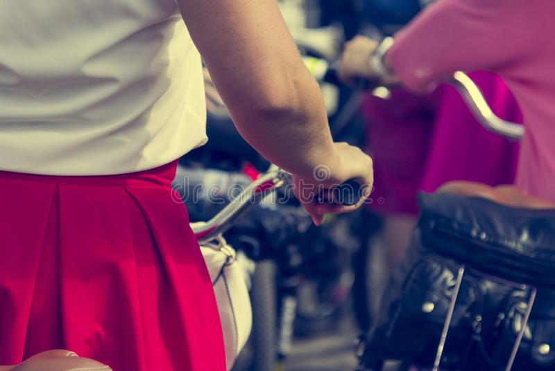 Poj?cie: kobiety na bicyklach Kobieta w jaskrawych ubraniach trzyma handlebars Część obrazek obraz stock