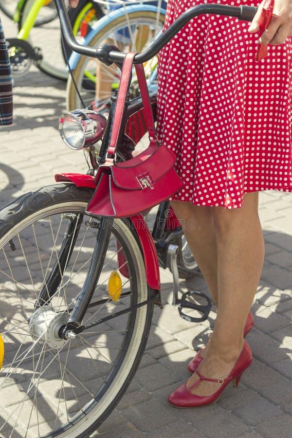 Poj?cie: kobiety na bicyklach R?ki trzyma handlebars Dziewczyna jest ubranym czerwoną polki kropki spódnicę zdjęcia stock