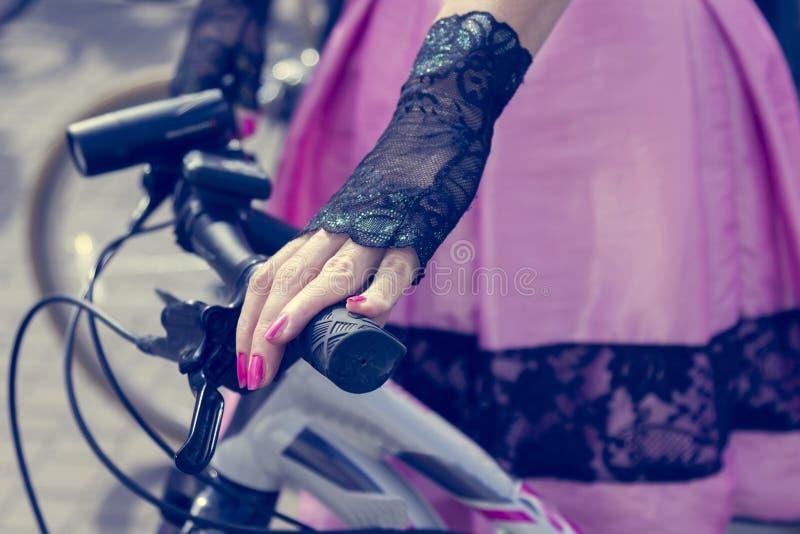 Poj?cie: kobiety na bicyklach R?ki trzyma handlebars R??owa sp?dnica z czerni koronk? obraz stock
