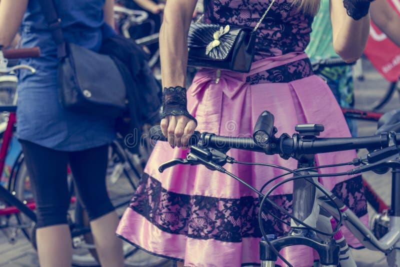 Poj?cie: kobiety na bicyklach R?ki trzyma handlebars R??owa sp?dnica z czerni koronk? zdjęcie royalty free