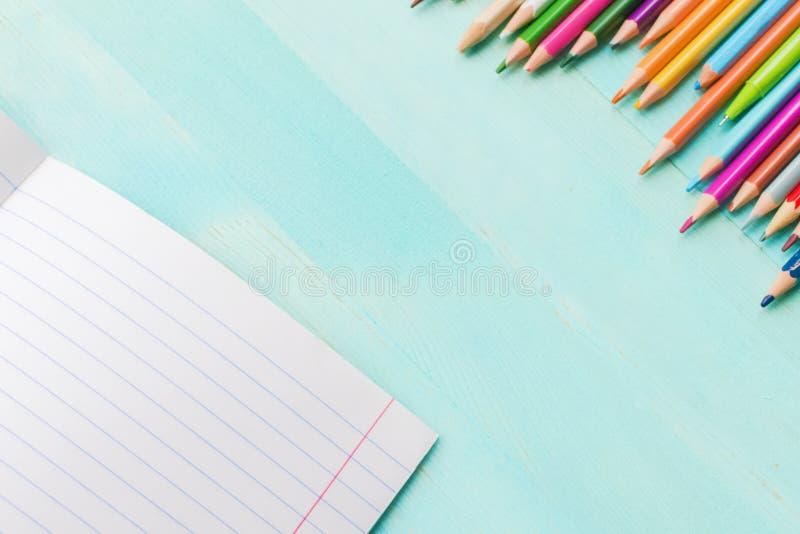 Poj?cie z powrotem szko?a Szkolni akcesoria, barwioni ołówki, pióro z pustym notatnikiem na błękitnym drewnianym tle fotografia royalty free