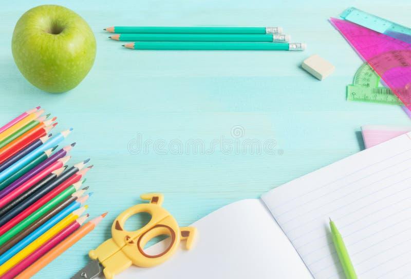 Poj?cie z powrotem szko?a Szkolni akcesoria, barwioni ołówki, pióro z pustym notatnikiem na błękitnym drewnianym tle fotografia stock