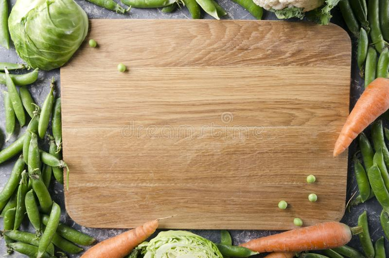 Poj?cie zdrowy jedzenie i przepisy Tn?ca deska i udzia? zieleni wiosen warzywa tak jak zieleni grochy, marchewki, m?oda kapusta E zdjęcia stock