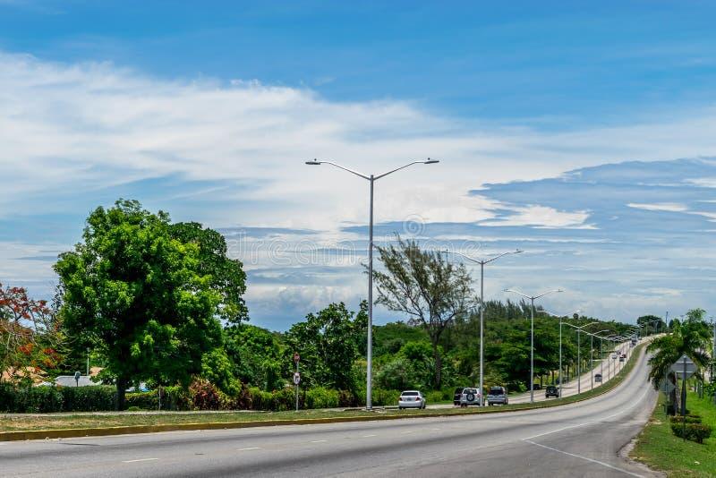 Pojazdu je?d?enie wzd?u? Eleganckiej korytarz autostrady w Montego Bay, Jamajka Samochody jad? na lewej r?ki stronie droga fotografia stock