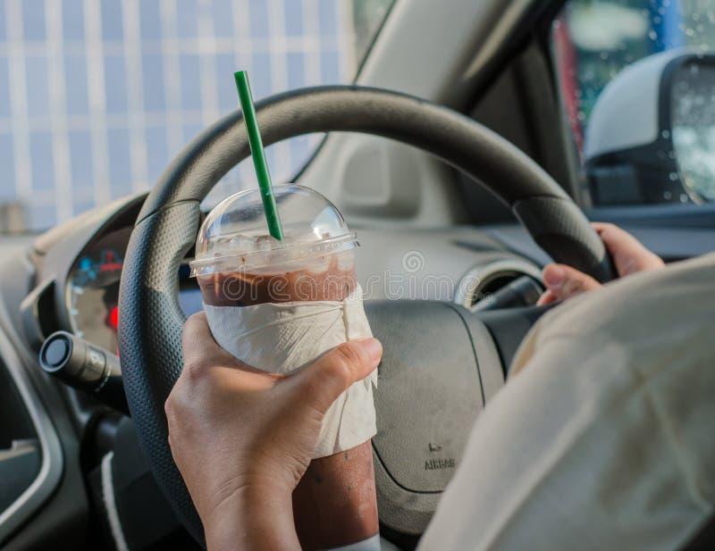 Pojazdu pojęcie - obsługuje pić kawę podczas gdy jadący samochód zdjęcie royalty free