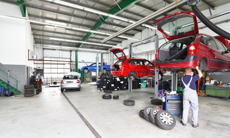 Pojazdy w samochodowym remontowym sklepie na podnośnej platformie dla naprawy obraz stock