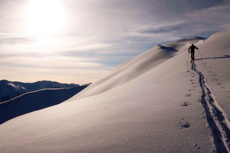 Pojedyncza męska backcountry narciarka wspina się śnieżną grań blisko Klosters zdjęcia stock